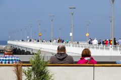Tourists spend their free time near the pier royalty free stock photos