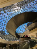 Tourists and spiral staircase inside glass pyramid in Louvre, Paris, France Stock Photography