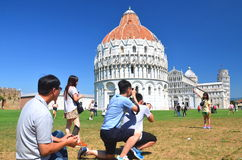 Tourists on Square of Miracles visiting Leaning Tower in Pisa, Italy Stock Photos