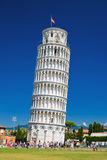 Tourists on Square of Miracles visiting Leaning Tower in Pisa, Italy. Leaning Tower of Pisa is campanile and is one of the most famous buildings in the world Royalty Free Stock Photo