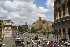 Tourists in the heart of Rome, Italy. Tourists on the square near the Colosseum and the Arch of Constantine in front of ruins of the Temple of Venus and Rome Royalty Free Stock Photo