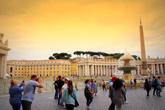 Tourists on St Peter`s square Vatican. Tourists sightseeing on St. Peter`s square or Piazza San Pietro Vatican with one of the fountains created by Carlo Maderno Stock Photos
