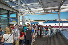 Tourists stand in anticipation of the pleasure boat on the quay. ST. PETERSBURG, RUSSIA - JULY 10, 2016: Tourists stand in anticipation of the pleasure boat on Royalty Free Stock Photos
