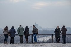 Tourists standing on Kalemegdan fortress looking at a foggy panorama of Novi Beograd, the most modern part of Belgrade. BELGRADE, SERBIA - FEBRUARY 21, 2015 stock photography