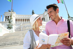 Tourists standing near Vittoriano with book in hands Stock Photos