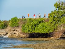 Tourists standing on reef in Benoa Bali stock image