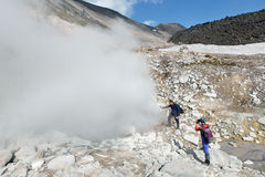 Tourists standing by smoking fumaroles on crater active volcano. Royalty Free Stock Photo
