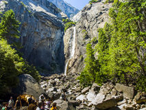 Tourists standing submontane of the lower Yosemite waterfall Stock Image