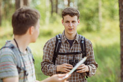 Tourists standing in the woods, talking and looking through bino Stock Images