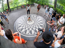 Tourists at Strawberry Fields in Central Park in New York. NEW YORK, USA - AUGUST 21, 2015 : Small child at the Imagine mosaic commemorating John Lennon at royalty free stock image