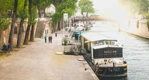 Tourists stroll along the Seine beside the barges in Paris,. PARIS, FRANCE - May 08, 2017: tourists stroll along the Seine beside the barges in Paris, France royalty free stock photo