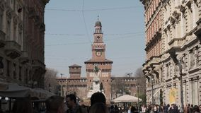 Tourists stroll along Via Dante in Milan and the Sforza castle in the background. Italy stock video