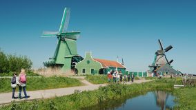 Zaanse Schans, Netherlands, May 2018: Tourists stroll around the old mills in the folkloric village of Zaanse Schans. Tourists stroll around the old mills in the stock video footage