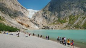Brigsdal, Norway, July 2018: Tourists stroll by the lake, formed from the meltwater of the Brixdal Glacier. Tourists stroll by the lake, formed from the stock video footage