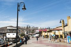 Tourists Stroll Past Shops at Ensenada Harbor. ENSENADA, MEXICO - OCTOBER 22, 2018: Tourists stroll by the shops and restaurants on the waterfront of Ensenada stock photo