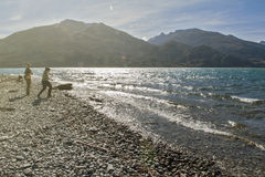 Tourists strolling around Lake Wanaka, New Zealand, in the late afternoon. Stock Images