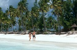 Tourists strolling on a white beach in Zanzibar Stock Photo