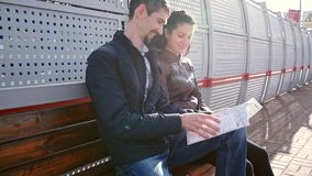 Tourists study map and wait for train. Man and girl are studying map and waiting for train stock video