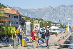 Tourists with suitcases, backpack and bags walk along the yachts and motorboats moored at the pier. Muo, Montenegro – October 13, 2018: Tourists with stock images