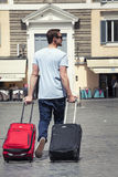 Tourists and suitcases. Man with suitcases in the historic center of Rome, Italy. A tourist is walking with two suitcases. One red and one black. The man in the Stock Image