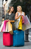 Tourists with suitcases and shopping bags. Two cheerful girls with suitcases and shopping bags standing in the street Royalty Free Stock Photography