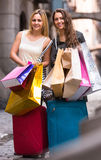 Tourists with suitcases and shopping bags. Two cheerful smiling girls with suitcases and shopping bags standing in the street Royalty Free Stock Photography