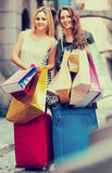 Tourists with suitcases and shopping bags. Two cheerful smiling girls with suitcases and shopping bags standing in the street Stock Image