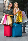 Tourists with suitcases and shopping bags. Two happy smiling girls with suitcases and shopping bags standing in the street Stock Image
