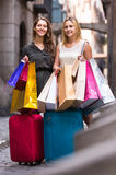 Tourists with suitcases and shopping bags. Two happy smiling young women with suitcases and shopping bags in the street Royalty Free Stock Image