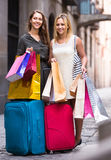 Tourists with suitcases and shopping bags. Two happy  young women with suitcases and shopping bags in the street Royalty Free Stock Photo