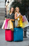 Tourists with suitcases and shopping bags. Two joyful girls with suitcases and shopping bags standing in the street Royalty Free Stock Image