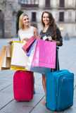 Tourists with suitcases and shopping bags. Two joyful smiling girls with suitcases and shopping bags standing in the street Stock Photo