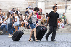 Tourists and suitcases. Two tourists walking through the city, they drag their heavy suitcases under the scorching sun / behind them many tourists sitting on the Royalty Free Stock Image
