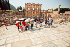 Tourists with sun umbrellas standing near Historical Celsus Library of Ephesus city Stock Photography