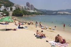 Tourists sunbathe at the Stanley town beachin Hong Kong, China. HONG KONG, CHINA - SEPTEMBER 16, 2012: Unidentified tourists sunbathe at the Stanley town beach stock image