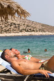 Tourists sunbathing at the beach of Ios Greek island, in Cyclade Stock Photos
