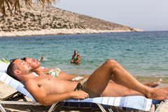 Tourists sunbathing at the beach of Ios Greek island, in Cyclade Royalty Free Stock Photography
