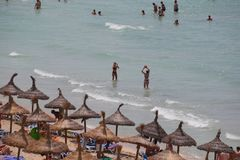 Tourists sunbathing or enjoying water sports in el arenal beach in mallorca royalty free stock image