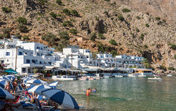 Tourists sunbathing and swimming in blue lagoon of Loutro town at Crete island Stock Photo