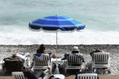 Tourists, sunbeds and umbrellas on summer hot day. mediterranean sea beach in Nice, France. Royalty Free Stock Photos