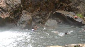 Tourists Swim in Foamy Pool at Waterfall in Tropical Park. People tourists swim in foamy river pool near waterfall foot among rocks in tropical park in Vietnam stock footage