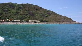 Tourists swim on island beach against restaurants stock video