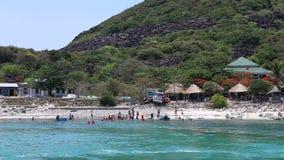 Tourists swim on island beach against restaurants stock video footage