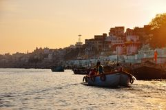 Tourists take a boat tour on the Ganges River in Varanasi, India. Tourists take a boat tour on the Ganges River during a sunset in Varanasi, India royalty free stock photo