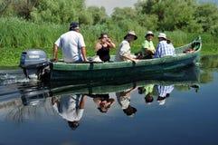 Tourists take boat trip in the Danube Delta Biosphere Reserve. SULINA - JUNE 25:Unidentified tourists take boat trip with a local guide in the Danube Delta royalty free stock image