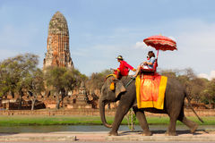Tourists take an elephant ride around historic site at Wat Phra Ram, in Ayutthaya, Thailand. The imposing Wat Phra Ram temple can be seen in the background Stock Image