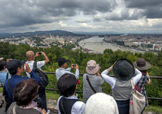 Tourists take photographs of the Danube River in Budapest in Hungary. Tourists take photographs of the Danube River from the CitadelFortress on Gellert Hill in royalty free stock image