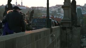 PRAGUE, CZECHIA - 12TH APRIL 2019: Tourists on the famous Charles Bridge during early Sunset during the Easter Holidays stock video footage
