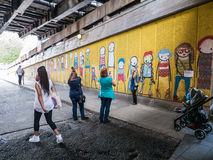 Tourists take photos in front of street graffiti under South Ban Stock Images