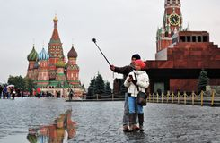 Tourists take pictures with mobile phone on the Red Square in Moscow. Saint Basils cathedral, Lenin`s mausoleum and Saviors tower at background. Color photo Stock Image